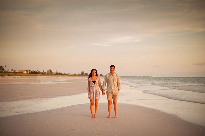Couple standing on st pete beach at low tide during engagement session