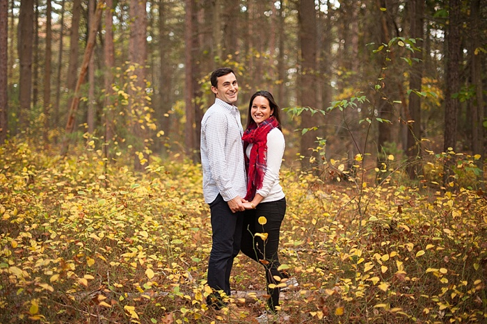 Couple taking fall engagement photos in Fells Reserve Park