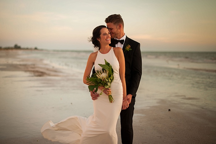 Bride and Groom Sharing a tender moment on St Pete beach in front of the Don Cesar