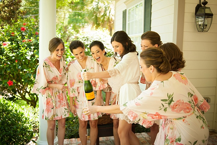 Brides tribe popping champagne while getting ready